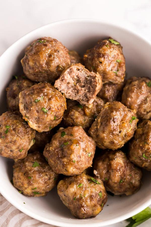 close up image of meatballs with one bite out of one meatball