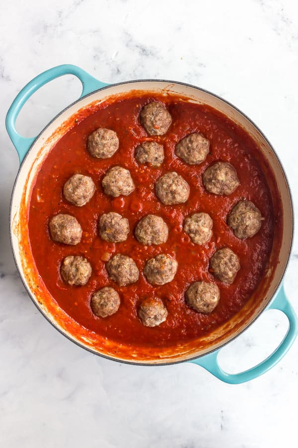 overhead image of meatballs placed in tomato sauce in large pan