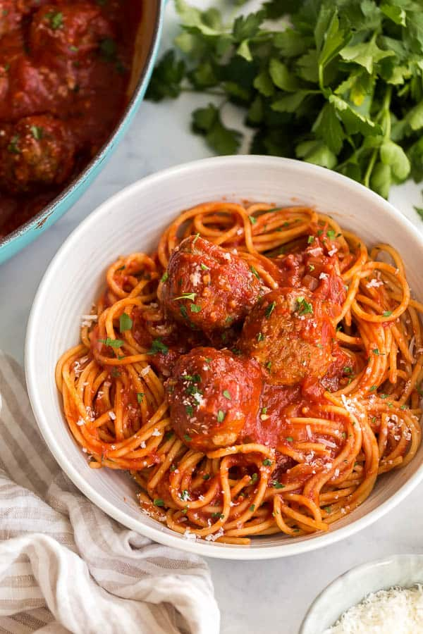 close up of spaghetti and meatballs in white bowl