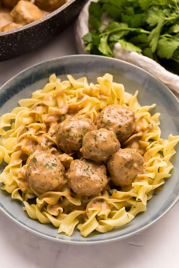close up image of swedish meatballs on a plate of egg noodles
