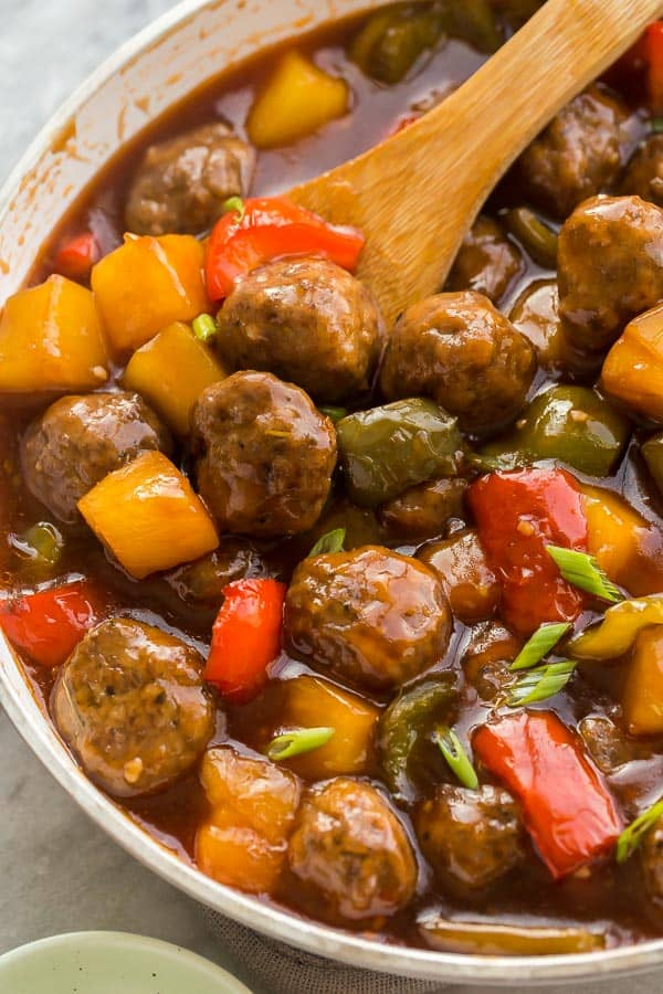 close up image of meatballs in pan with peppers and pineapple