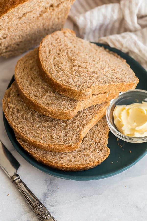 four slices of whole wheat bread on plate with butter