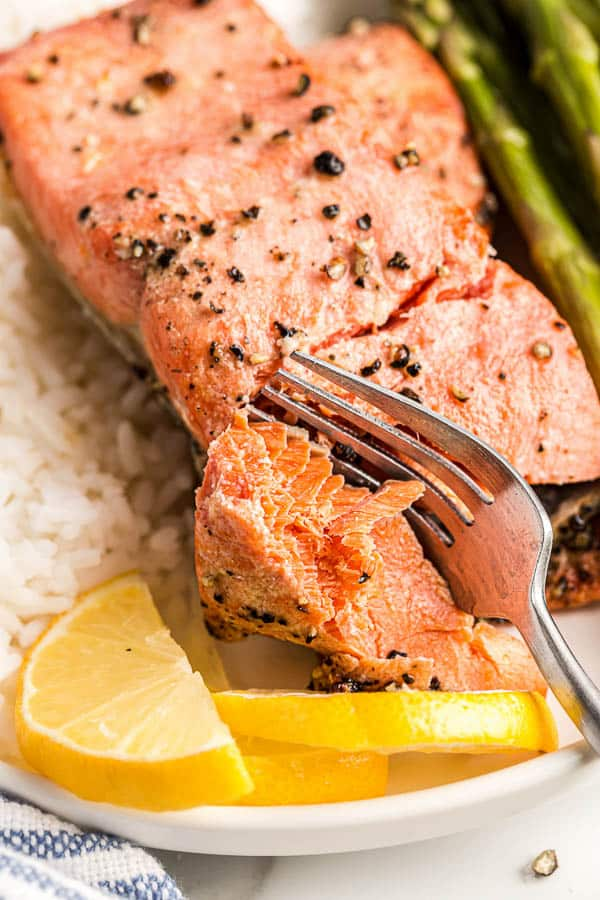 close up image of salmon flaking with fork