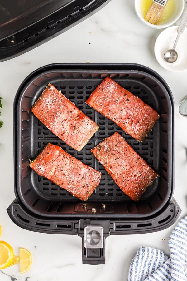 uncooked salmon fillets in air fryer basket