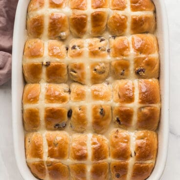 overhead image of hot cross buns in white baking dish with glaze