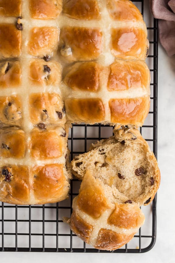 hot cross buns on black cool rack with one broken open