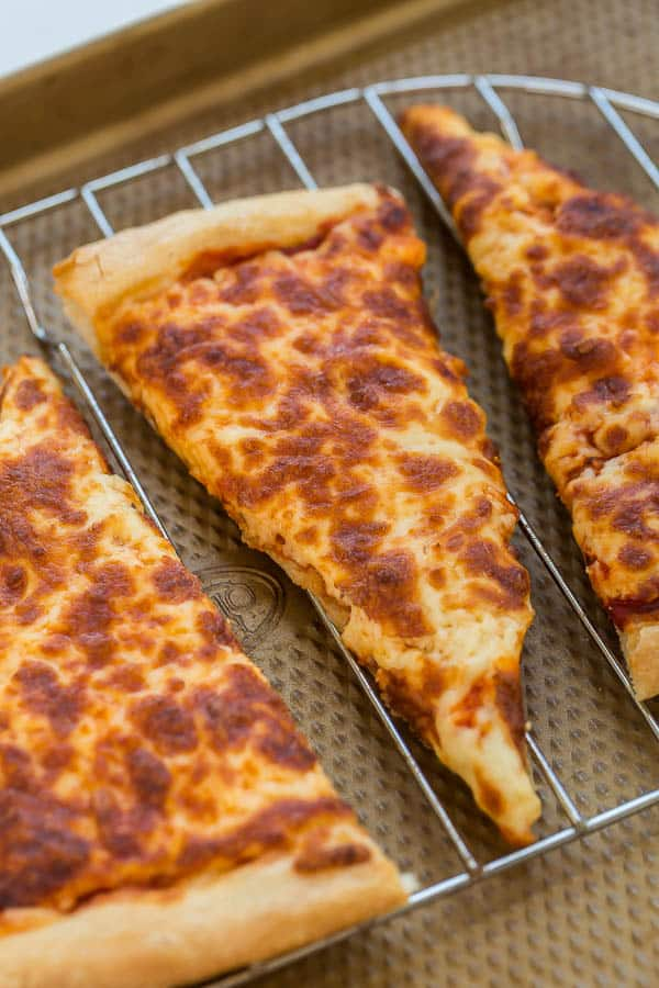 close up image of pizza slice on rack on sheet pan