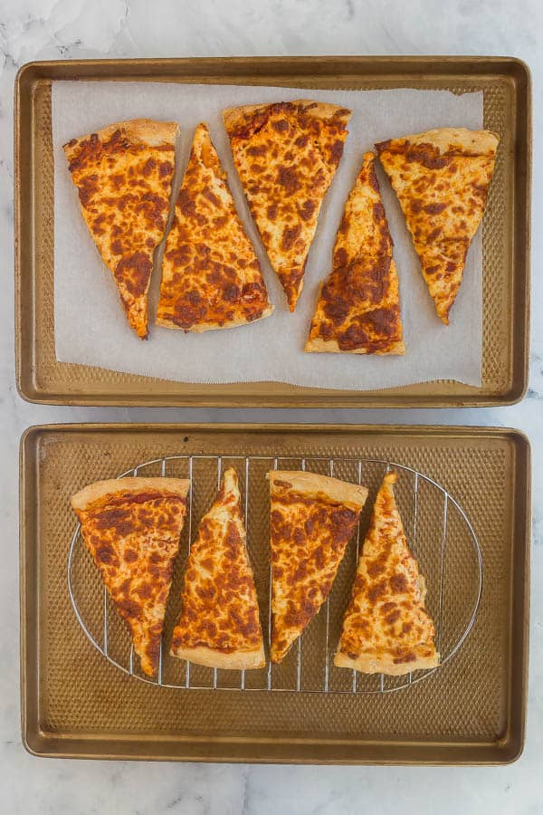 leftover pizza slices on baking sheet with rack and parchment