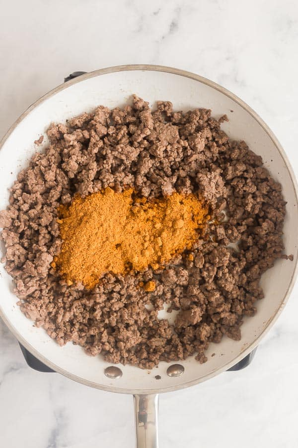 cooked ground beef in pan with taco seasoning