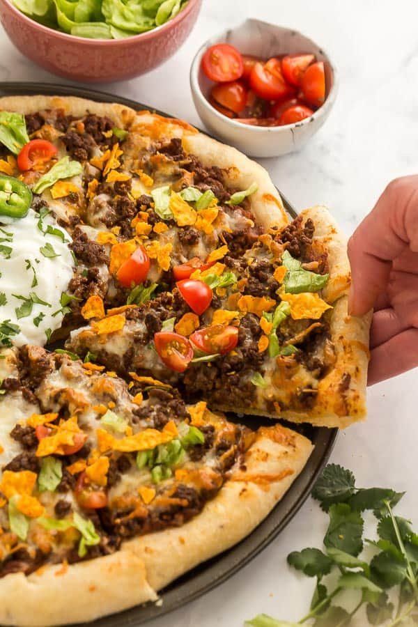 hand pulling out slice of taco pizza