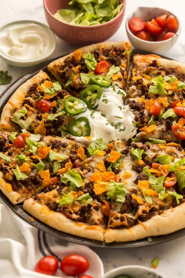close up image of taco pizza with lettuce tomatoes and chips