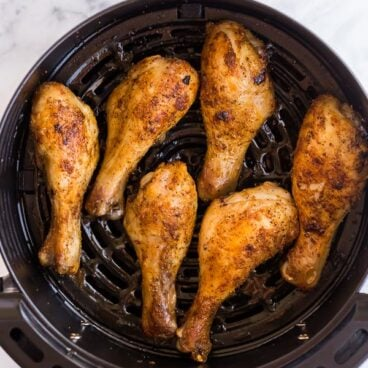 overhead image of cooked chicken drumsticks in air fryer basket