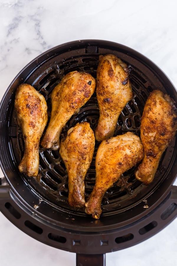 overhead image of cooked chicken drumsticks in air fryer basket