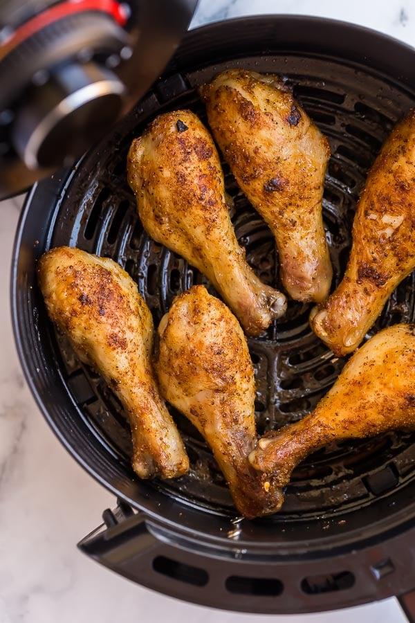 close up of crispy chicken legs in air fryer basket