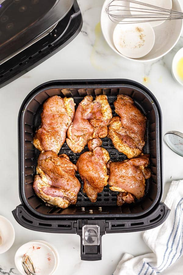 uncooked chicken thighs in air fryer basket