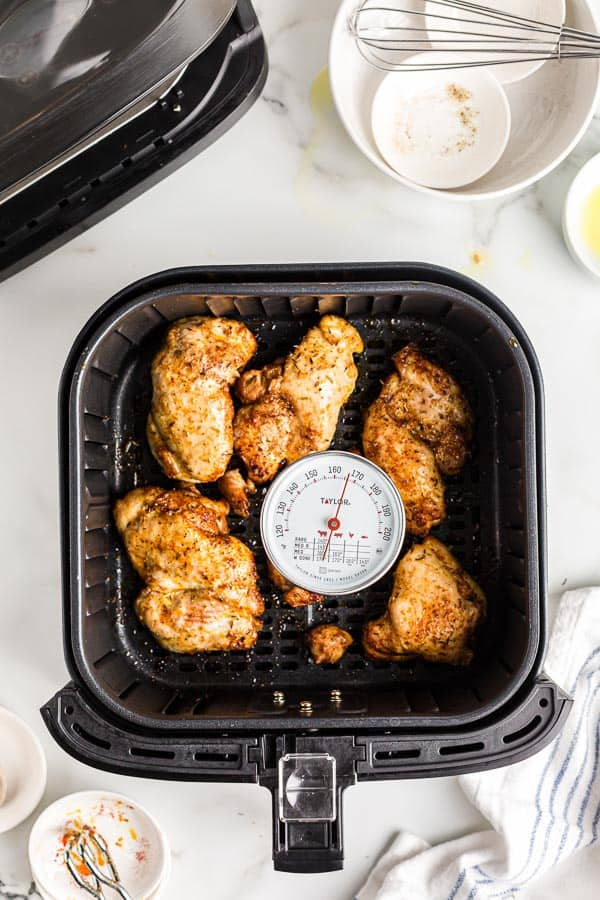 cooked chicken thighs in air fryer basket with thermometer at 165 degrees