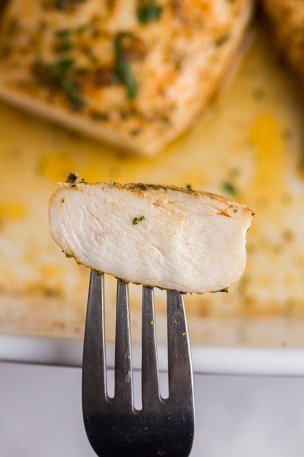 slice of baked chicken breast on fork