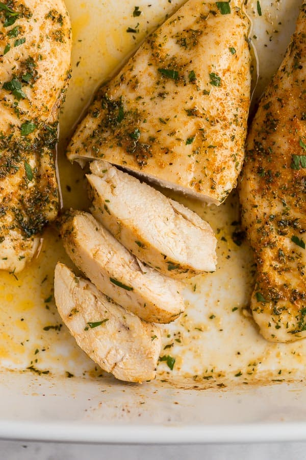 chicken breast in baking dish with three slices cut