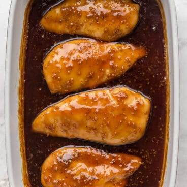 overhead image of honey garlic chicken breasts in baking dish