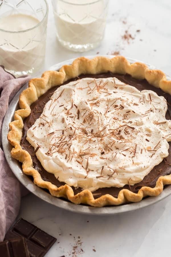 whole chocolate pie with whipped cream and two glasses of milk in the background