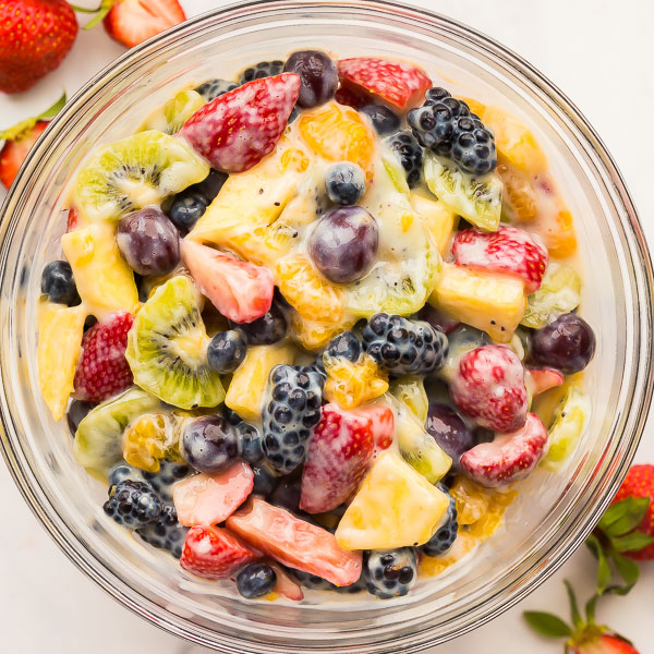 overhead image of creamy fruit salad in glass bowl on white background