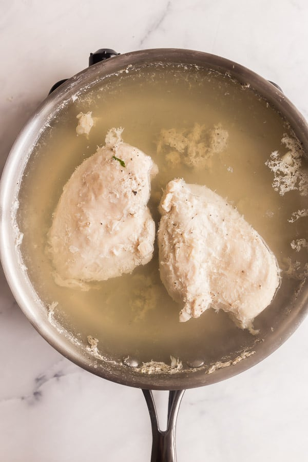 chicken breasts poaching in stainless steel pan