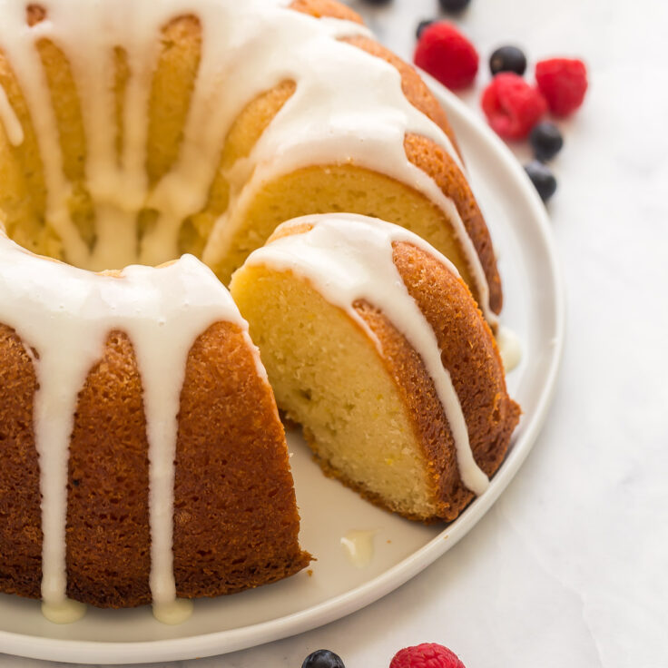 lemon bundt cake with glaze and one slice cut