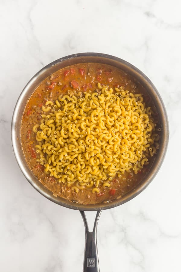 dry macaroni being added to skillet for taco mac