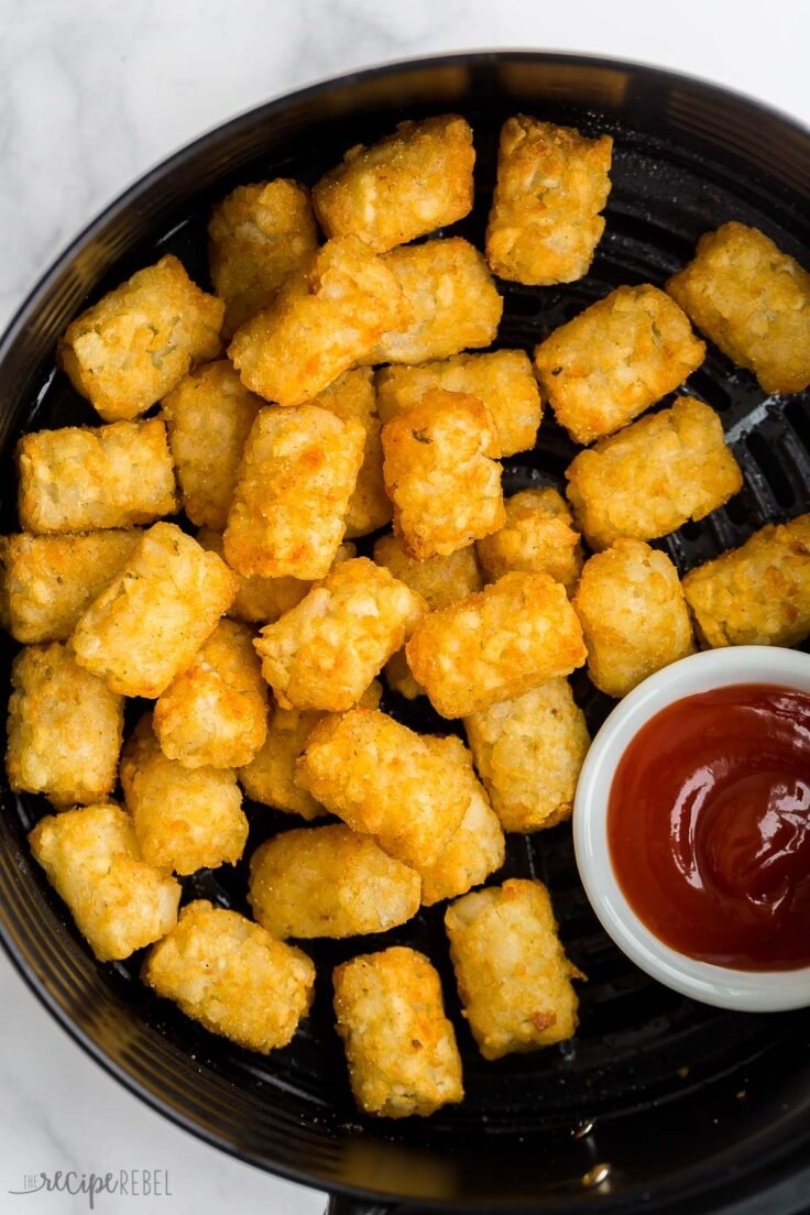 close up image of tater tots in air fryer with ketchup