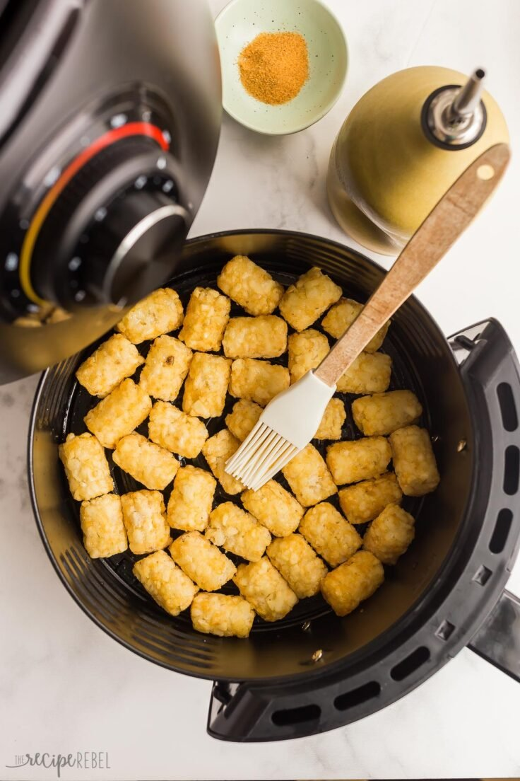 frozen tater tots in air fryer being brushed with oil