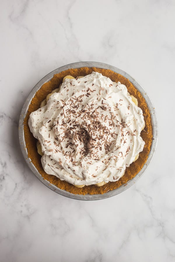 banoffee pie topped with whipped cream and chocolate shavings