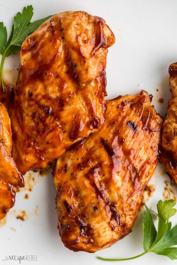 close up image of two grilled chicken breasts with bbq sauce