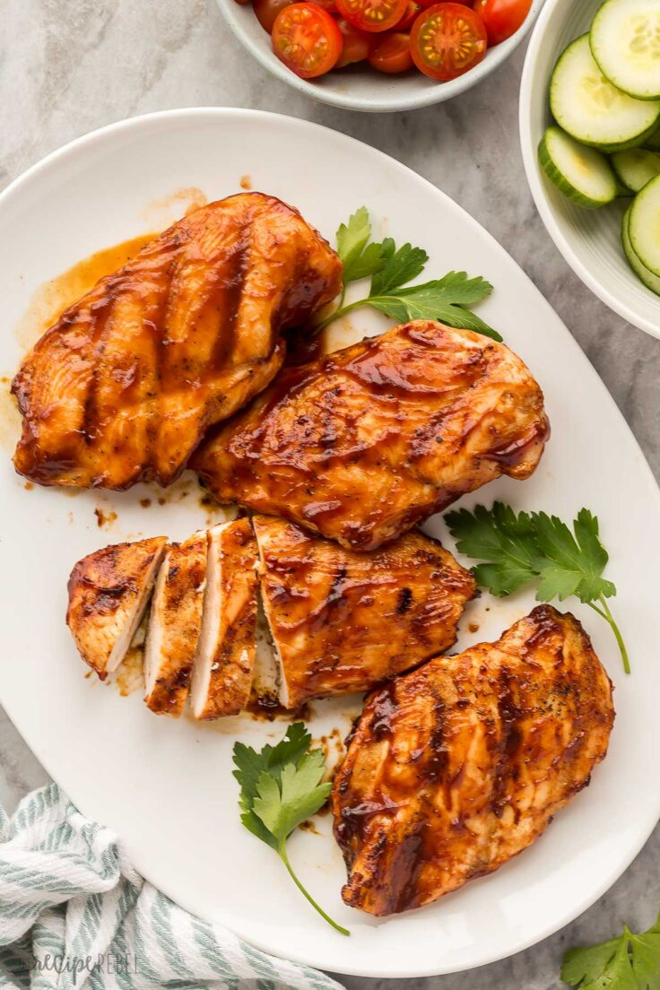 overhead image of four bbq chicken breasts with vegetables on the side