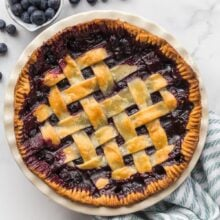 overhead image of baked blueberry pie with fresh blueberries