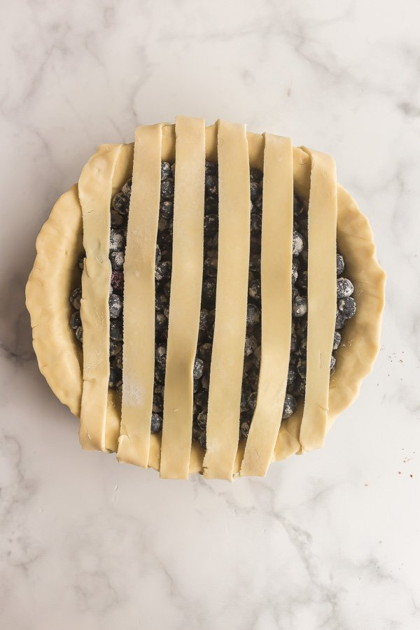overhead image of blueberry pie crust with pie crust strips in one direction