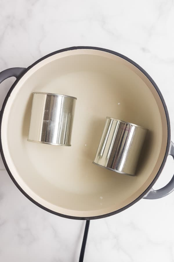 two cans of sweetened condensed milk in pot of water