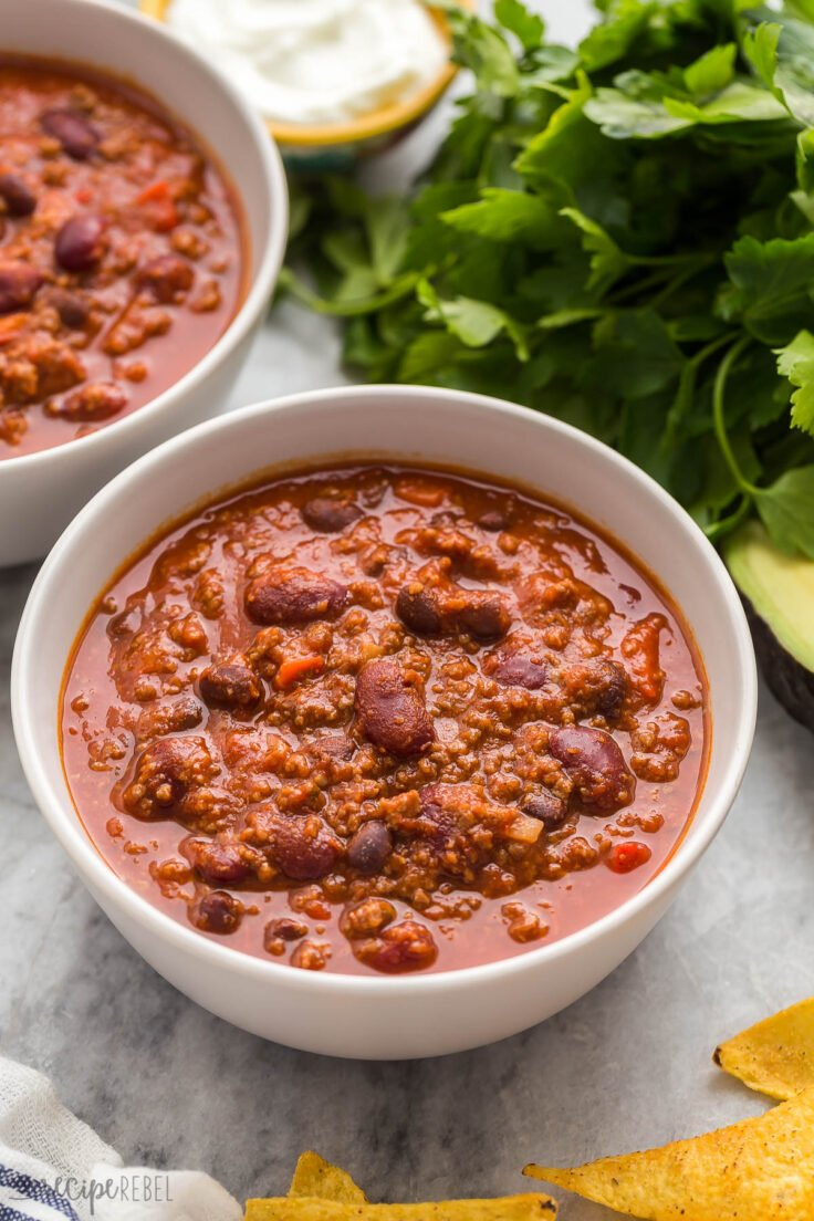 instant pot chili in a grey bowl with fresh parsley behind