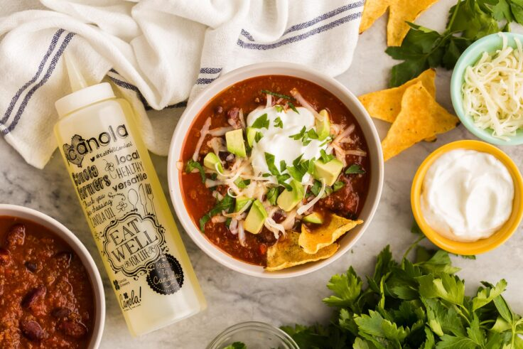 overhead image of instant pot chili with toppings and canola bottle