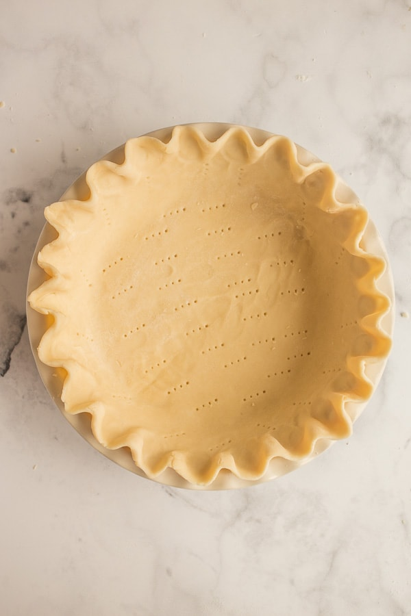 unbaked pie crust with edges crimped