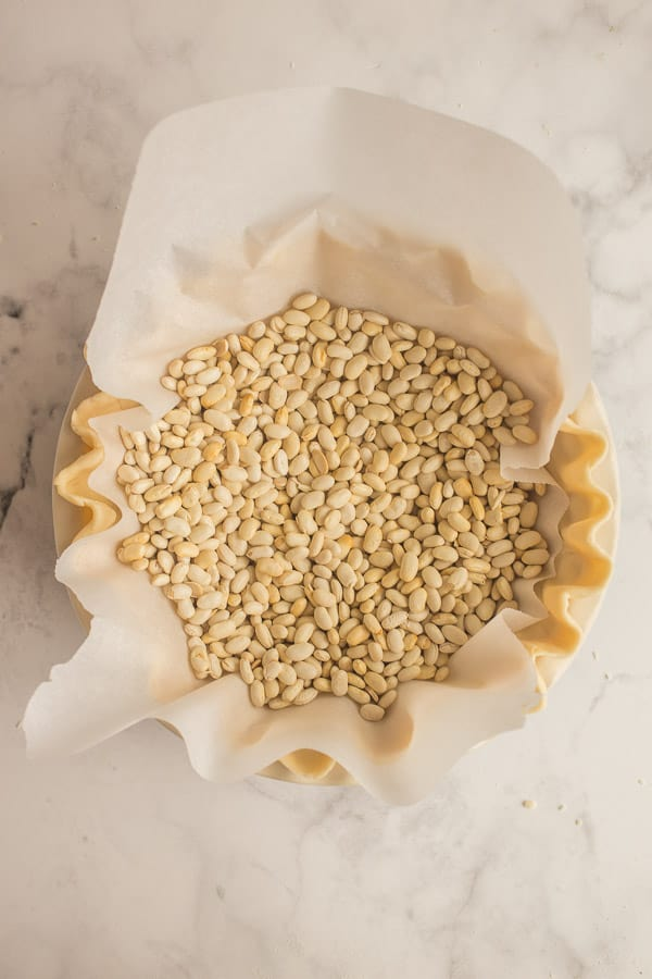 unbaked pie crust with parchment paper in the middle and pie weights