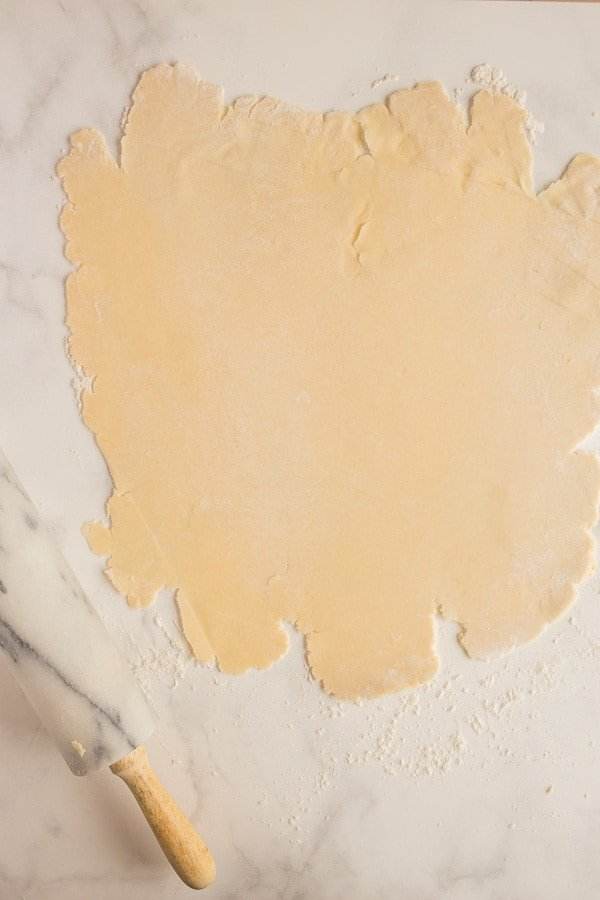 pie crust rolled out on marble with rolling pin