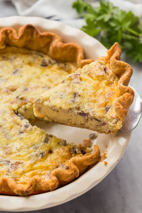 slice of quiche lorraine being lifted out of pie plate