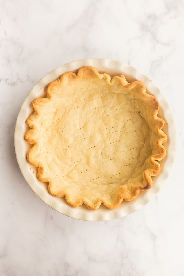 overhead image of blind baked pie crust on white background