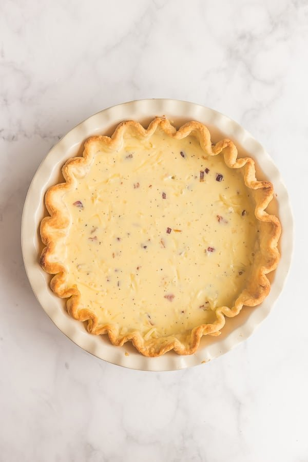 egg mixture added to blind baked pie crust for quiche