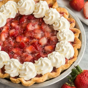 close up image of fresh strawberry pie with whipped cream