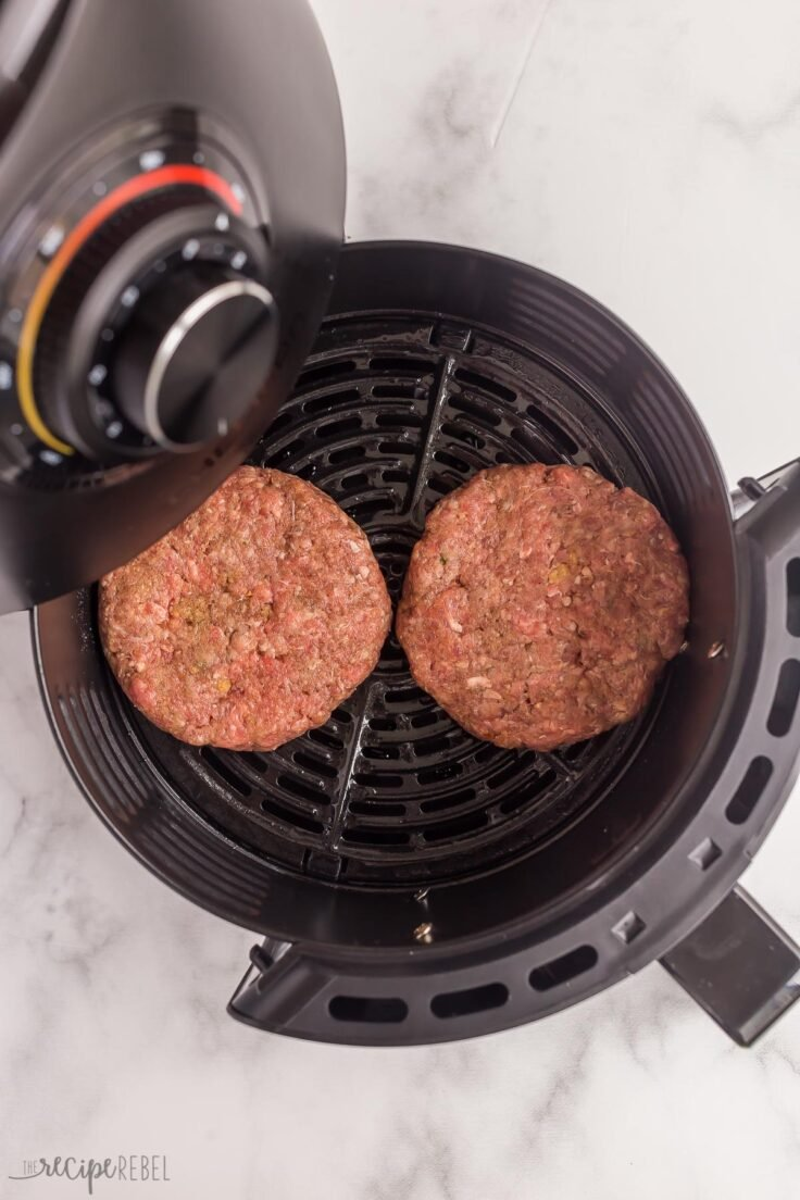uncooked burgers going into air fryer