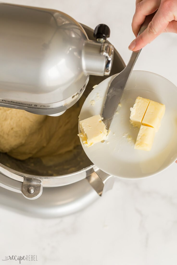 adding butter one tablespoon at a time to brioche bun dough
