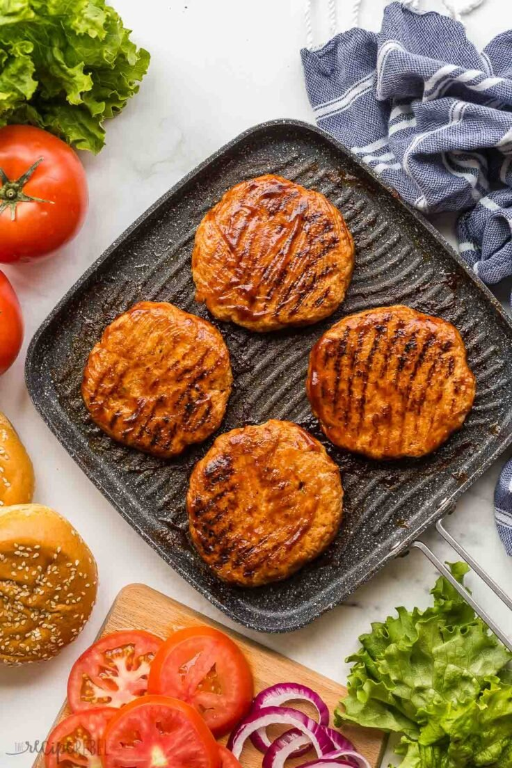 overhead image of grilled chicken burgers in pan