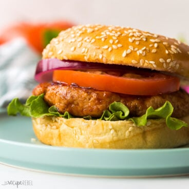 close up image of chicken burger in bun on blue plate