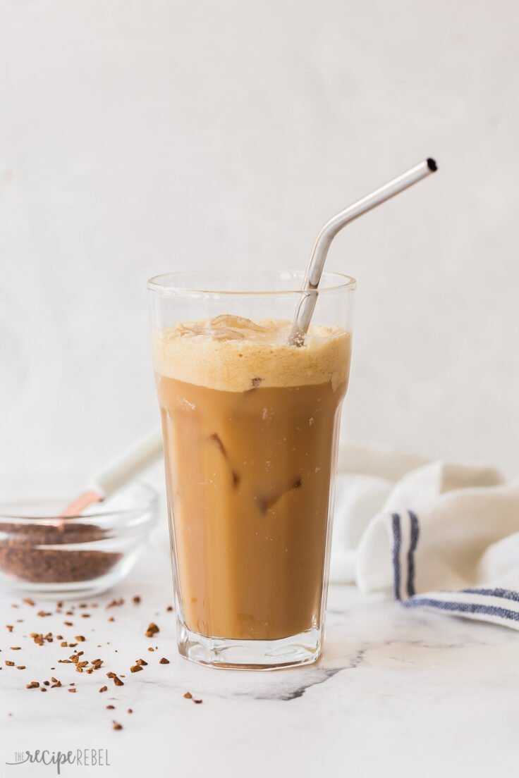tall glass of shaken coffee frappe with instant coffee in the background